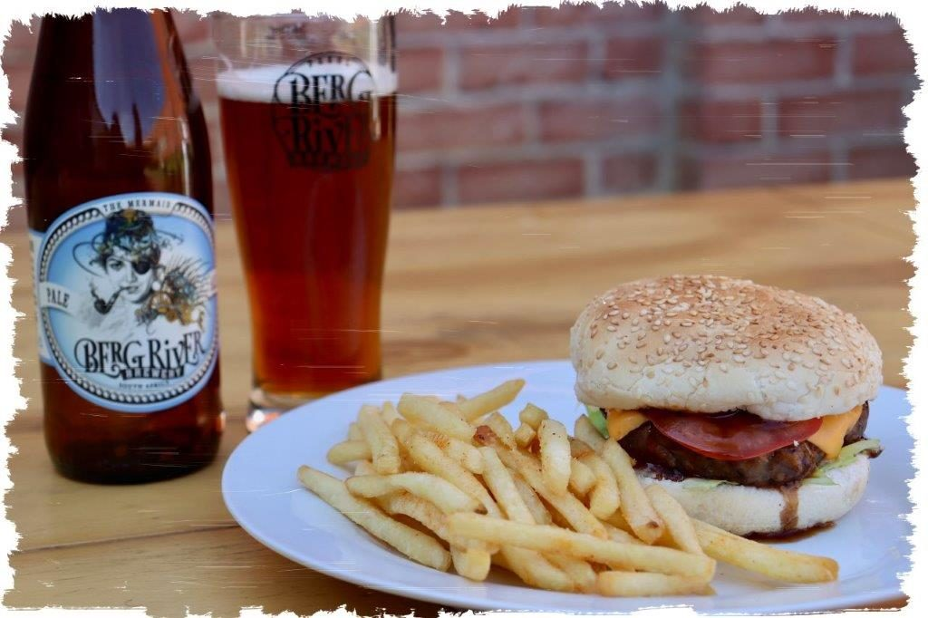 Craft Beer and Burgers offered at Berg River Brewery, Paarl. 150g pure beef burgers are topped with our famous BBQ sauce, feta, avo & bacon.